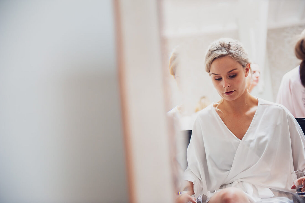 Bride in makeup chair mirror