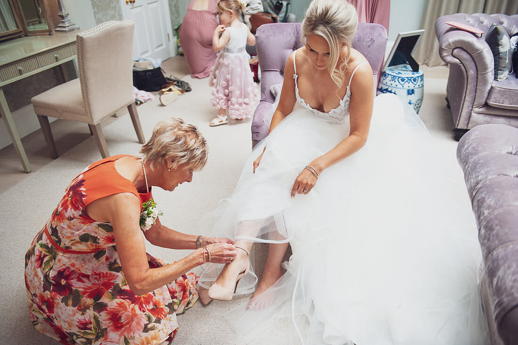 Bride adjusting shoes with mother