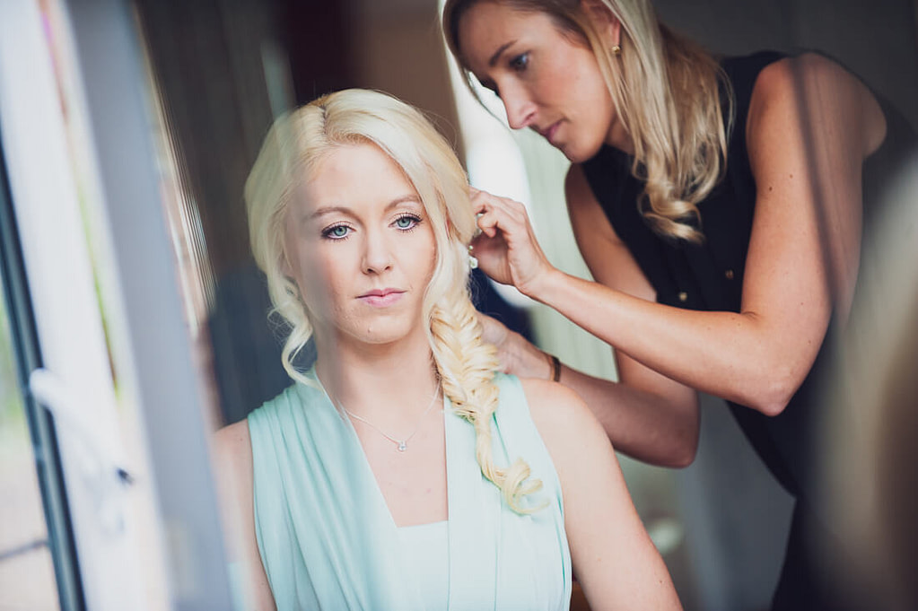 Bridesmaids hair being fixed in mirror