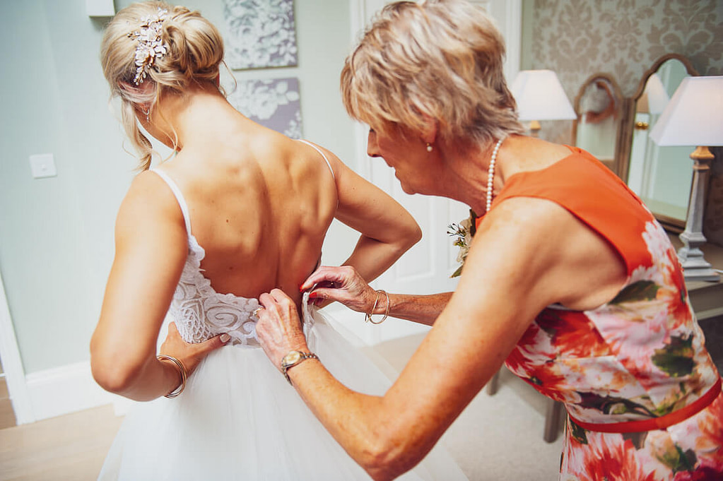 Bride helped in to dress