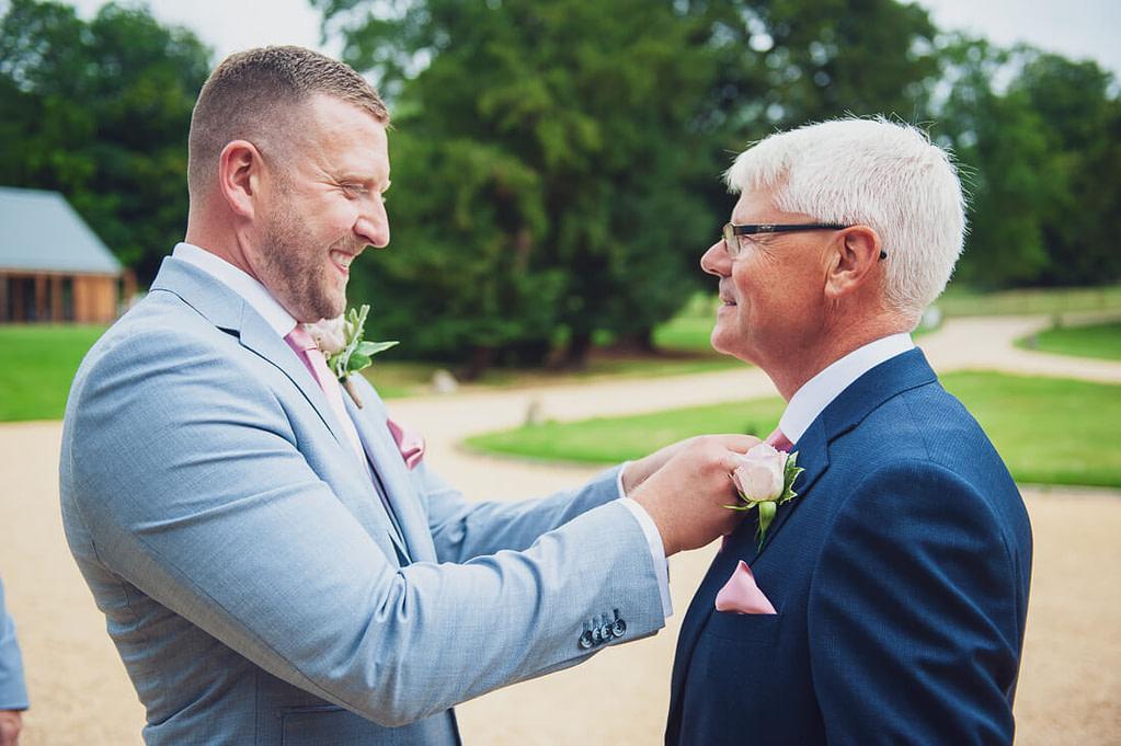 Groom adjusting fathers tie