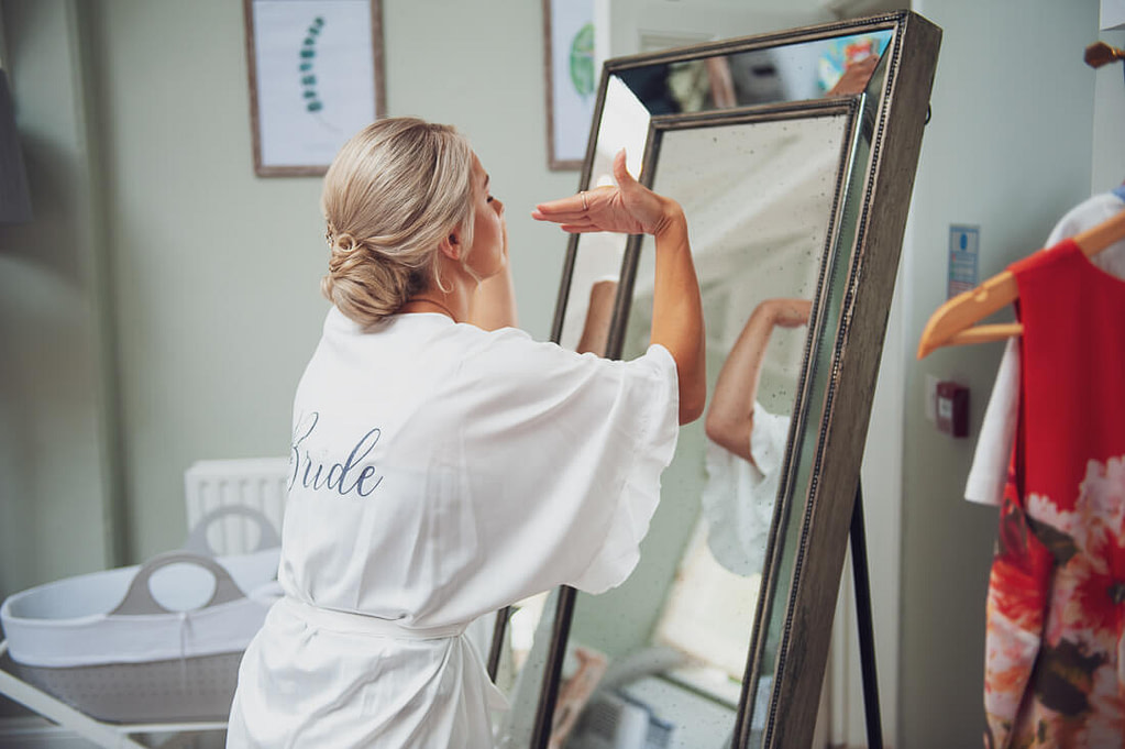 Bride drying makeup in mirror
