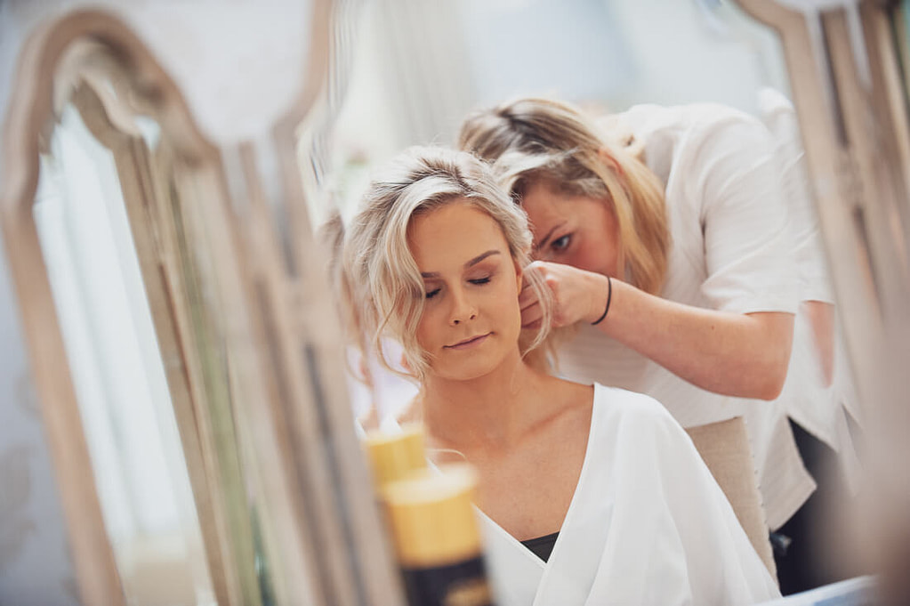 Bride in mirror and hairdresser